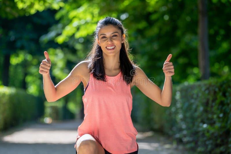 Gelukkig portret van het sportieve meisje glimlachen bij de camera met haar omhoog duimen stock afbeeldingen