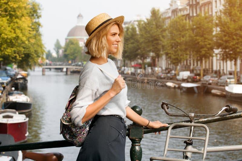 Gelukkig reizigersmeisje die van de stad van Amsterdam genieten Glimlachende vrouw die aan de kant op het kanaal van Amsterdam, N royalty-vrije stock foto