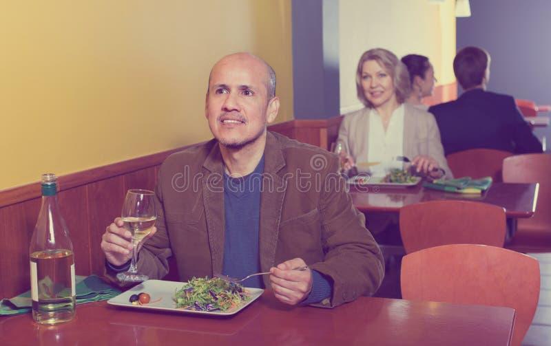 Gelukkig rijp mannetje die maaltijd met wijn hebben royalty-vrije stock foto's