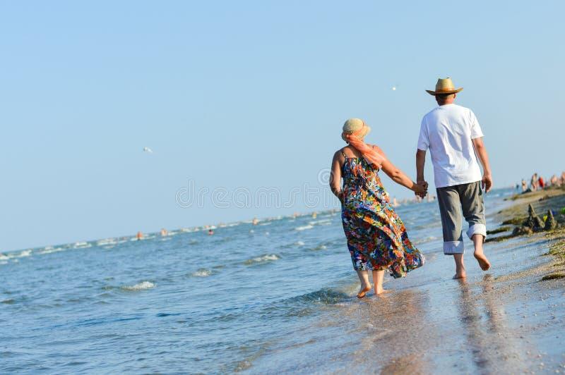 Gelukkig rijp paar die bij kust zandig strand lopen en handen houden royalty-vrije stock foto's