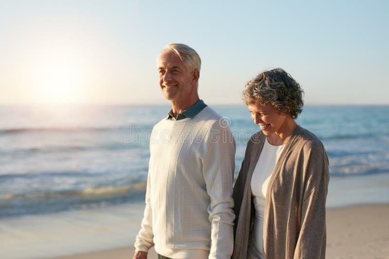 Gelukkig rijp paar die langs het strand lopen royalty-vrije stock afbeelding
