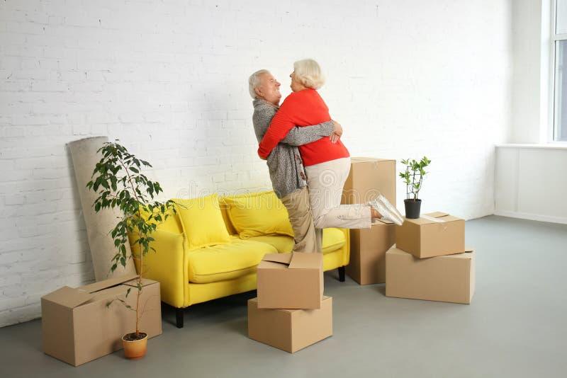 Gelukkig rijp paar met dozen na zich het bewegen in nieuw huis royalty-vrije stock fotografie