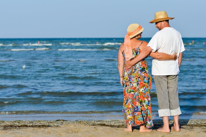 Gelukkig rijp romantisch paar die bij kust en het omhelzen rusten royalty-vrije stock afbeelding