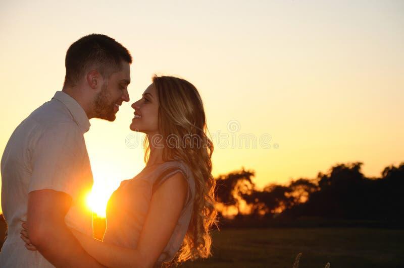 Gelukkig romantisch jong paar in liefde bij de zonsondergang royalty-vrije stock afbeeldingen