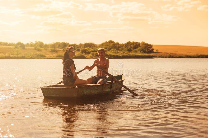 Gelukkig romantisch paar die een boot roeien stock fotografie