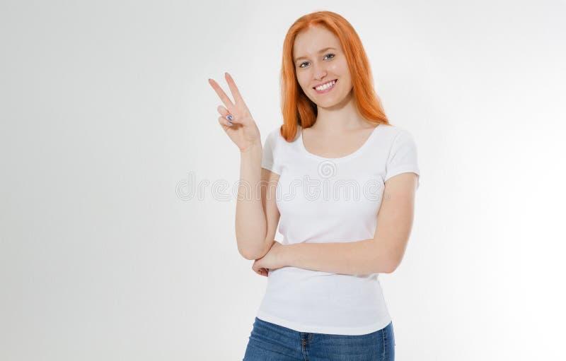 Gelukkig rood haarmeisje die camera met glimlach bekijken en vredesteken met vingers, jonge roodharigevrouw over het witte tonen  stock foto's