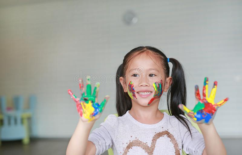 Gelukkig schilderden weinig Aziatisch meisje met haar kleurrijke handen en wang in de kinderenruimte Nadruk bij babygezicht stock fotografie