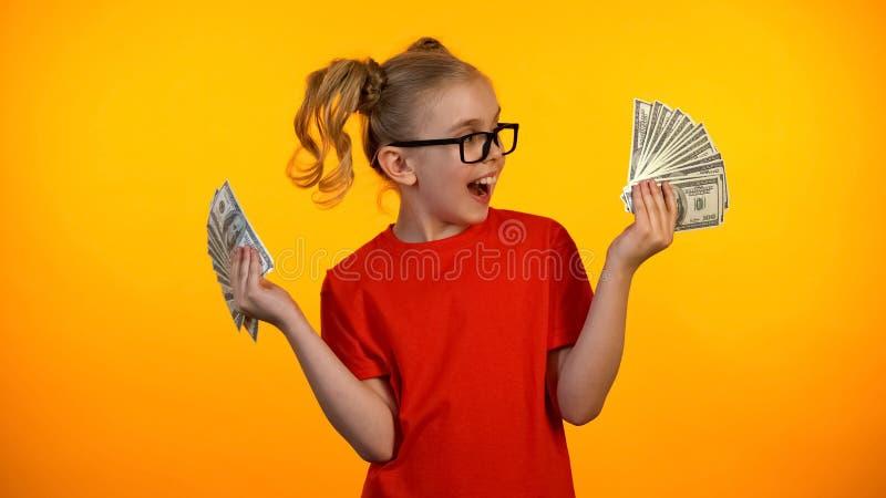 Gelukkig schoolmeisje die bossen van dollarcontant geld bekijken, slimme leerling die toelage ontvangen royalty-vrije stock afbeeldingen