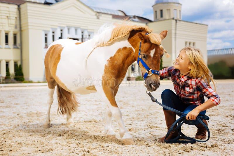Gelukkig schoolmeisje die vrolijk terwijl het communiceren met poney voelen royalty-vrije stock foto's