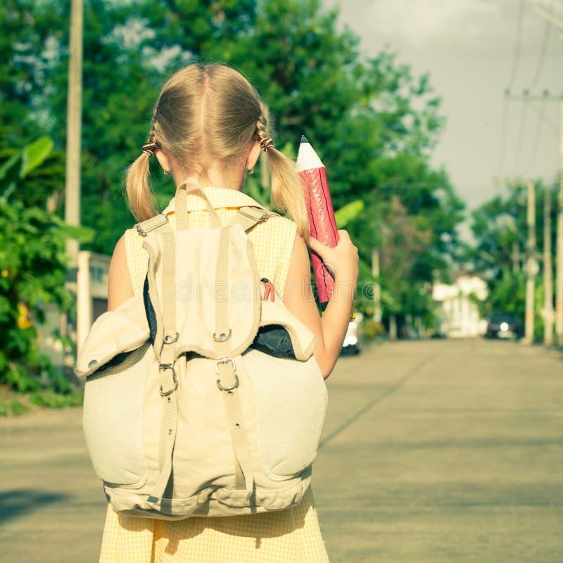 Gelukkig schoolmeisje die zich op de weg bevinden royalty-vrije stock foto's
