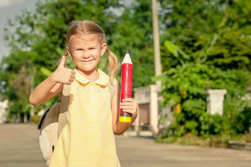 Gelukkig schoolmeisje die zich op de weg bevinden royalty-vrije stock afbeelding