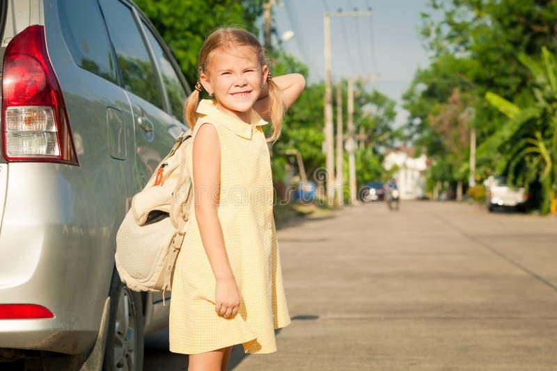 Gelukkig schoolmeisje die zich op de weg bevinden stock fotografie