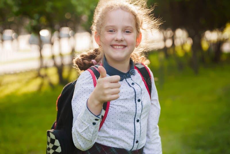 Gelukkig schoolmeisje met duimen op gebaar royalty-vrije stock fotografie