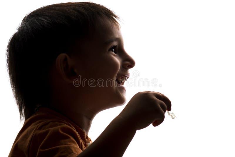 Gelukkig silhouet van weinig jongen die met zeepbels spelen royalty-vrije stock afbeelding