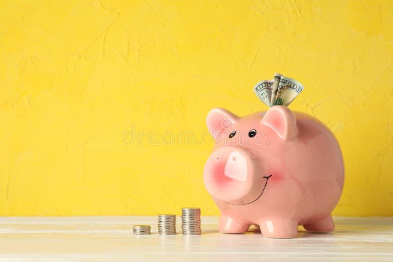 Gelukkig spaarvarken met geld op witte lijst tegen kleurenachtergrond, ruimte voor tekst royalty-vrije stock foto