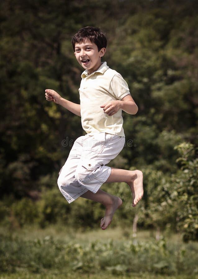 Gelukkig springt weinig jongen openlucht. stock afbeeldingen