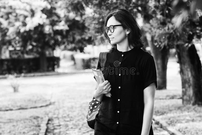 Gelukkig studentenmeisje in glazen met rugzak en boeken bij universitair park Vrouw met werkboeken die rust in campus hebben Onde royalty-vrije stock fotografie