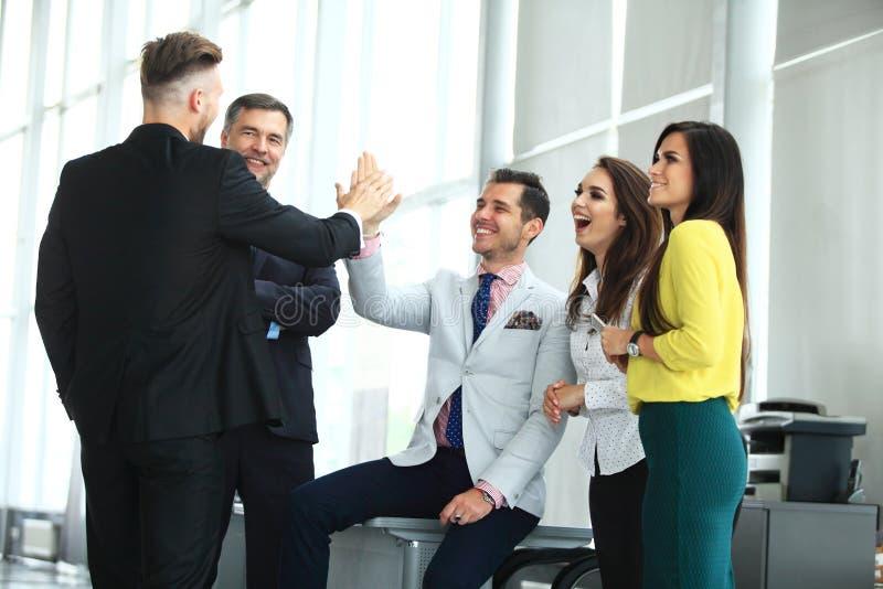 Gelukkig succesvol multiraciaal commercieel team die een hoog fivesgebaar geven aangezien zij lachen en hun succes toejuichen royalty-vrije stock foto