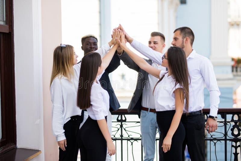 Gelukkig succesvol multiraciaal commercieel team die een hoog fivesgebaar geven aangezien zij lachen en hun succes toejuichen Com royalty-vrije stock foto's