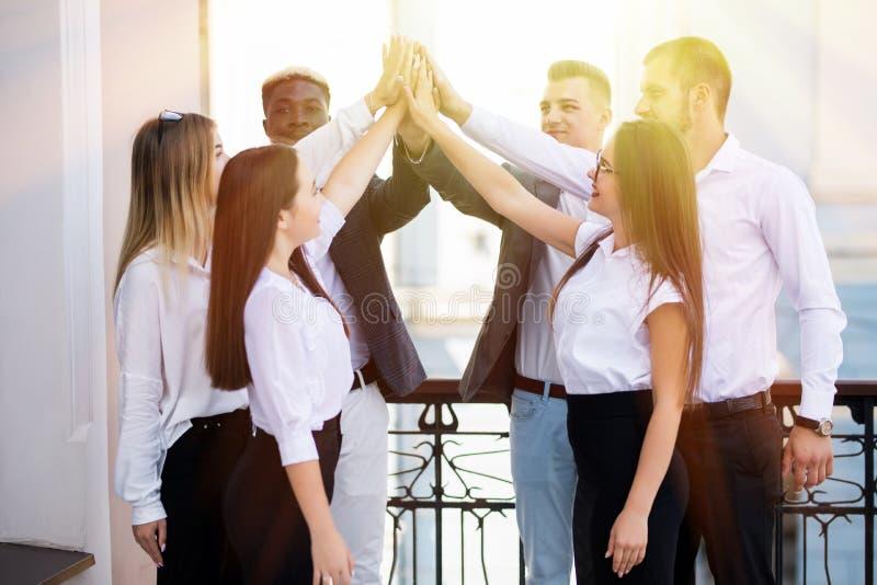 Gelukkig succesvol multiraciaal commercieel team die een hoog fivesgebaar geven aangezien zij lachen en hun succes toejuichen Com royalty-vrije stock foto