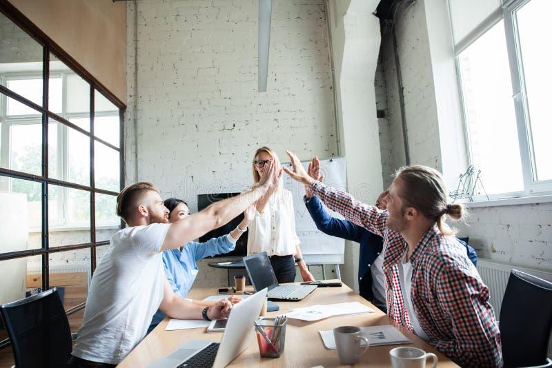 Gelukkig succesvol multiraciaal commercieel team die een hoog fivesgebaar geven aangezien zij lachen en hun succes toejuichen stock foto