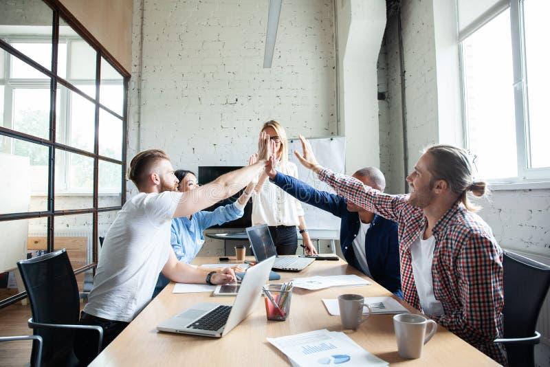 Gelukkig succesvol multiraciaal commercieel team die een hoog fivesgebaar geven aangezien zij lachen en hun succes toejuichen stock foto's
