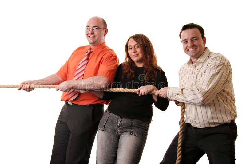 Gelukkig team in een touwtrekwedstrijd stock foto's
