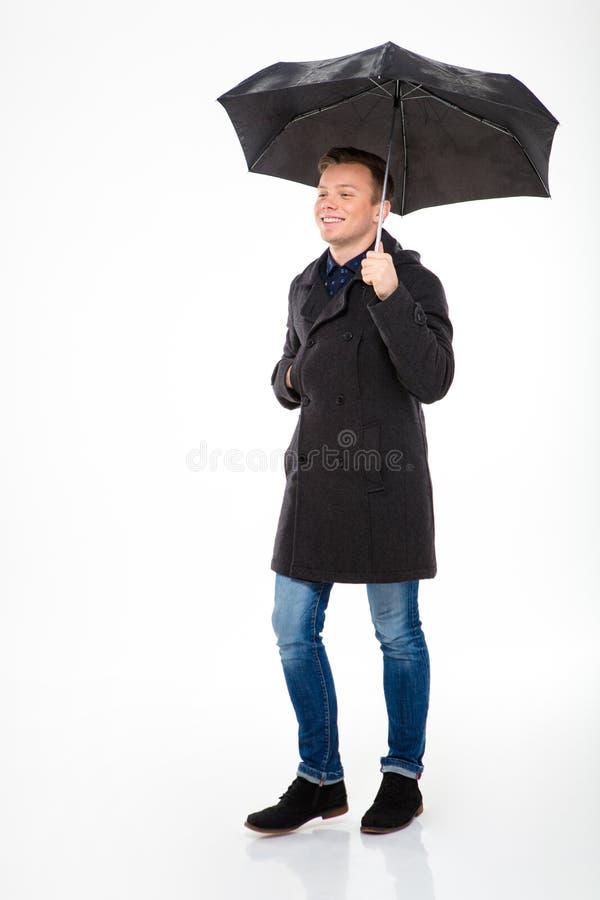 Gelukkig tevreden jong mannetje die in laag onder paraplu lopen stock foto's