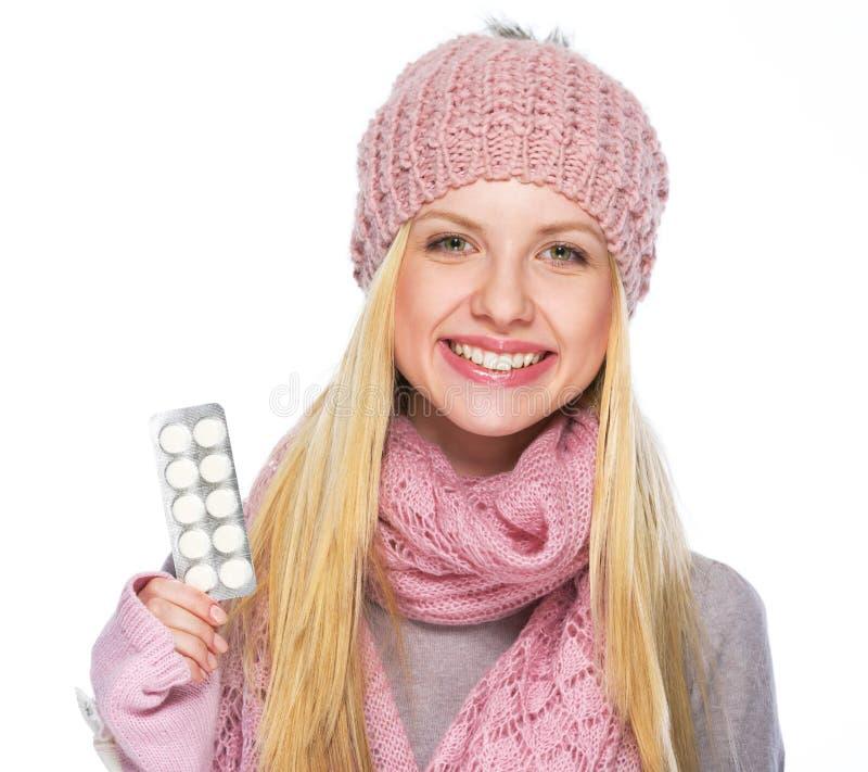 Gelukkig tienermeisje in de winterhoed en sjaal die pillenpak tonen royalty-vrije stock foto's