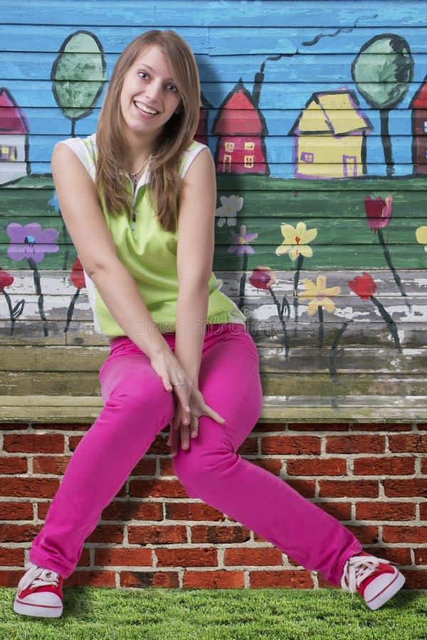 Het gelukkige glimlachende meisje van de lente op kleurrijke achtergrond stock afbeeldingen
