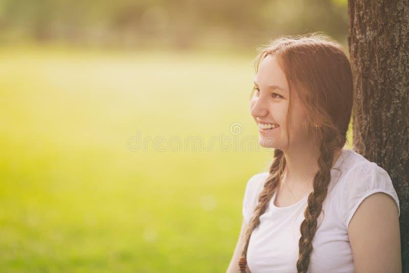 Gelukkig tienermeisje die in park onder boom rusten stock afbeeldingen