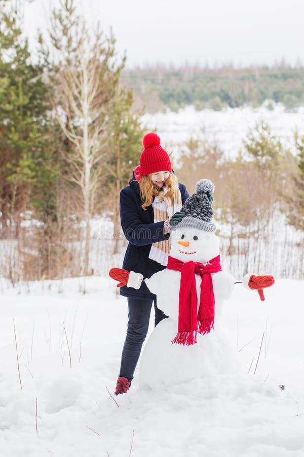 Gelukkig tienermeisje met sneeuwman stock foto