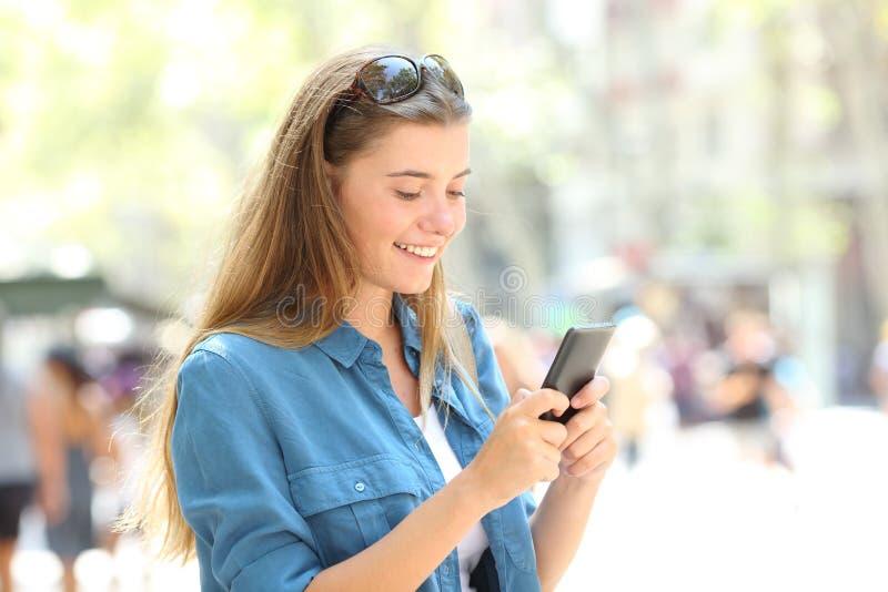 Gelukkig tieneroverseinen op smartphone in de straat stock foto