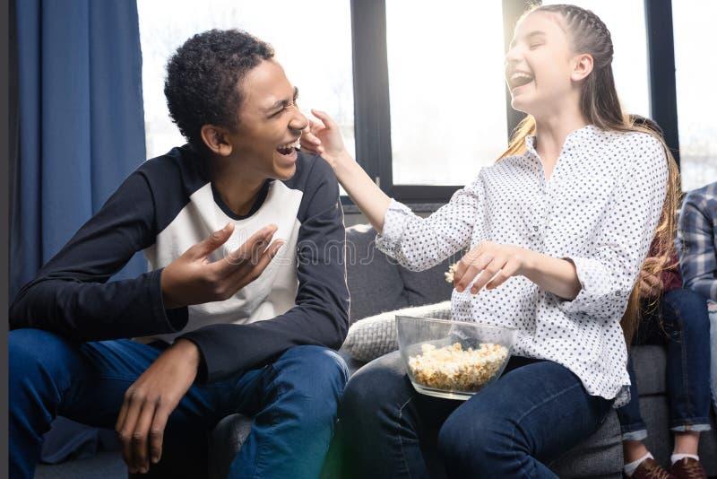 Gelukkig tienerpaar die popcorn van glaskom binnen eten stock afbeeldingen