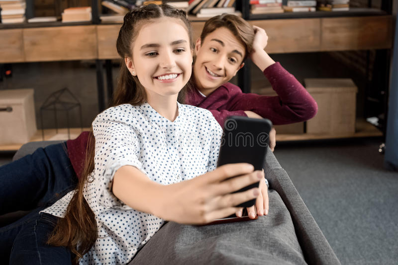 Gelukkig tienerpaar die selfie op smartphone nemen en op bank thuis zitten stock afbeeldingen