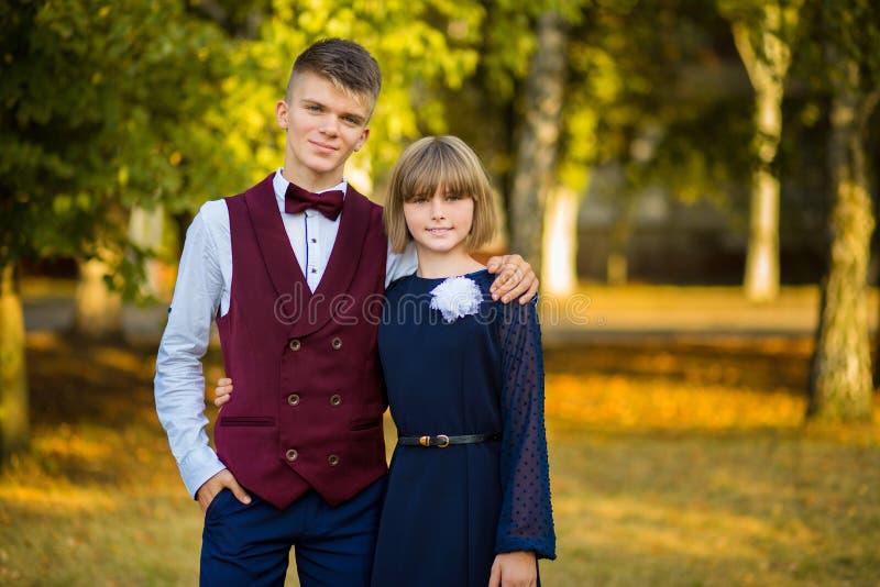 Gelukkig tienerpaar van middelbare schoolstudenten in feestelijke school eenvormig op achtergrond de herfstpark Begin van lessen stock afbeelding