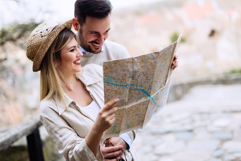 Gelukkig toeristenpaar met kaart die in openlucht reizen stock afbeeldingen