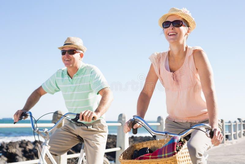 Gelukkig toevallig paar die voor een fietsrit gaan op de pijler stock fotografie