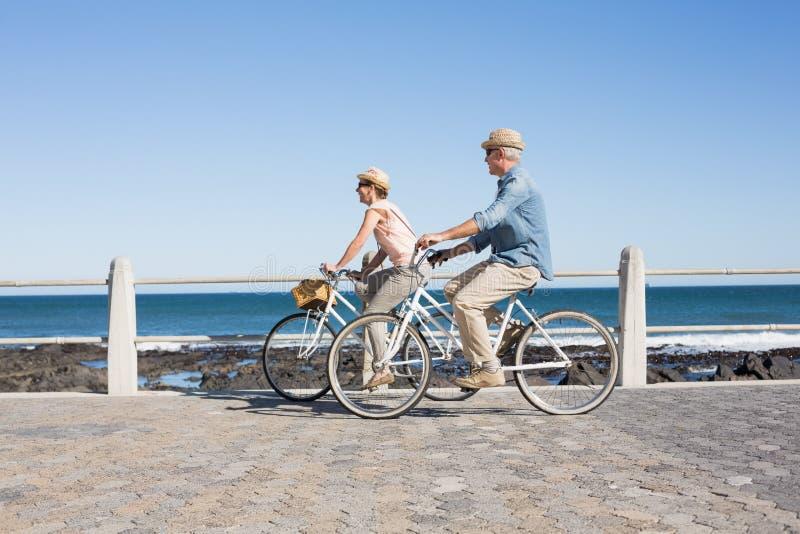 Gelukkig toevallig paar die voor een fietsrit gaan op de pijler royalty-vrije stock fotografie