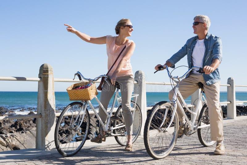 Gelukkig toevallig paar die voor een fietsrit gaan op de pijler royalty-vrije stock foto