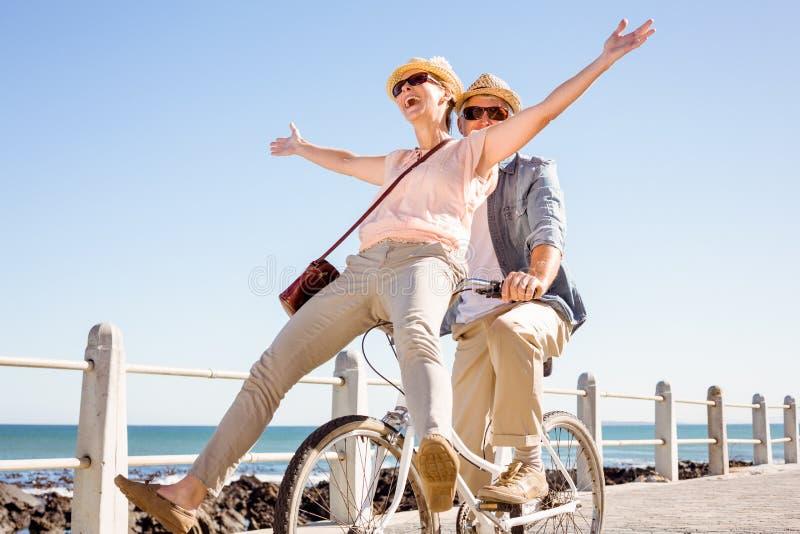 Gelukkig toevallig paar die voor een fietsrit gaan op de pijler stock foto