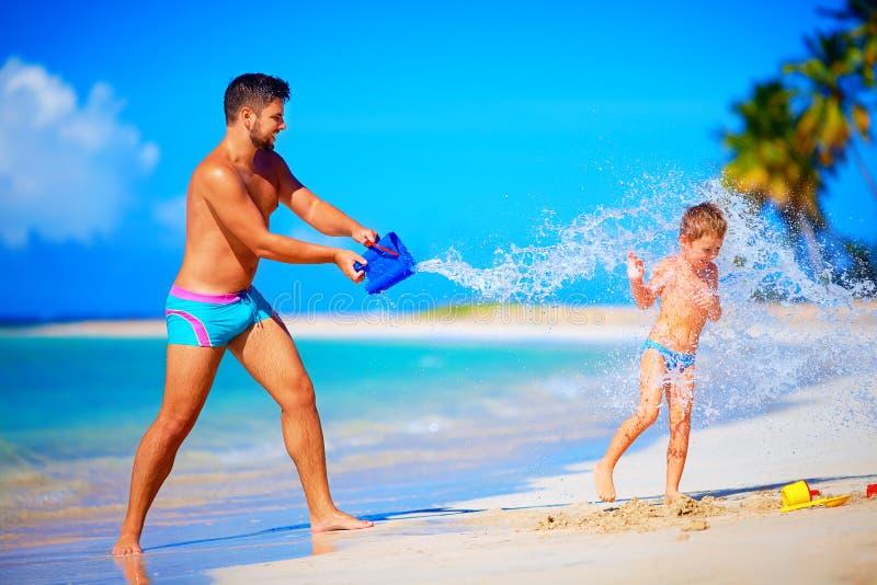 Gelukkig vader bespattend water op lachende zoon, de zomervakantie stock foto's
