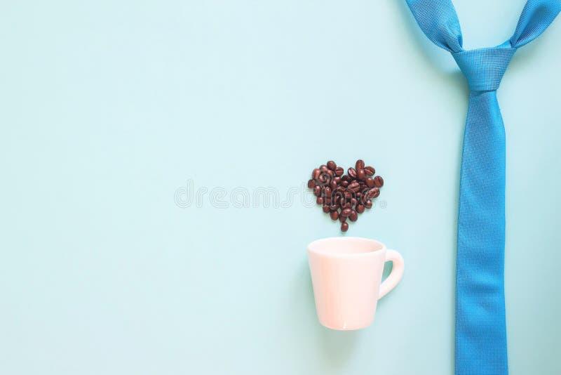 Gelukkig Vaderdagconcept met blauwe kleurenstropdas en koffiekop met het hartvorm van koffiebonen op pastelkleur stock afbeelding