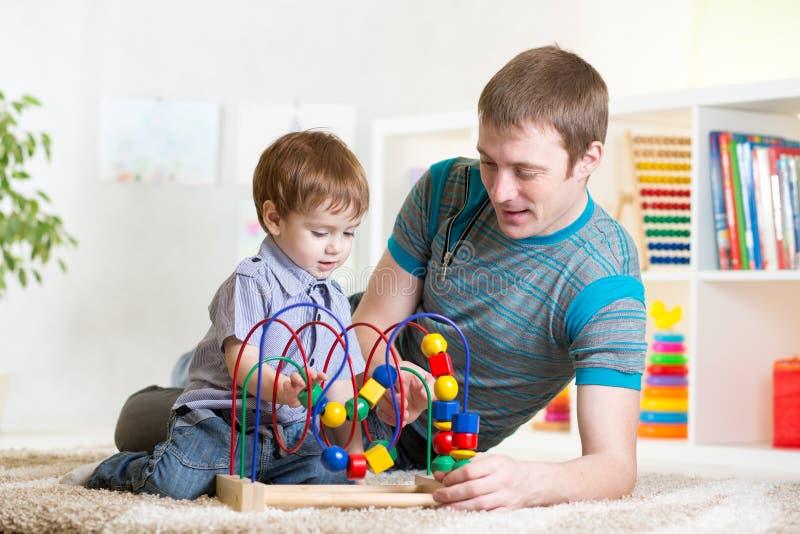 Gelukkig van de jong geitjejongen en papa het spelen stuk speelgoed stock fotografie