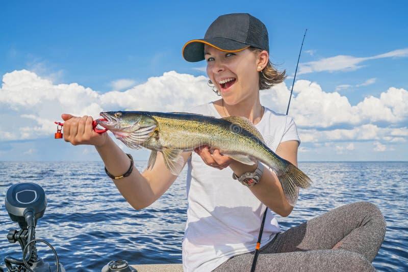 Gelukkig vissersmeisje met de trofee van snoekbaarzen zander vissen bij de boot royalty-vrije stock foto's