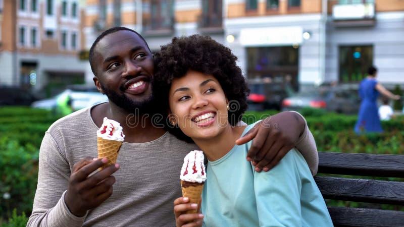 Gelukkig vriend en meisje die op bank, romantische datum met roomijs lachen stock fotografie