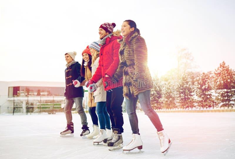 Gelukkig vriendenijs die op piste in openlucht schaatsen stock afbeelding