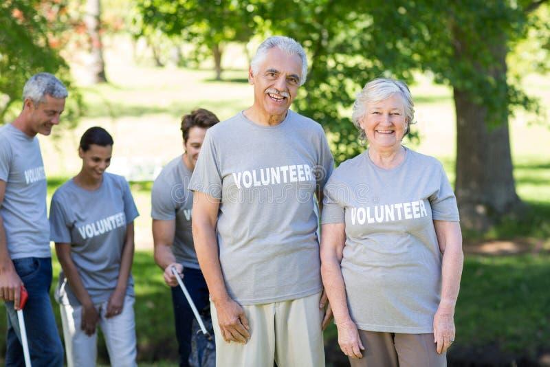 Gelukkig vrijwilligers hoger paar die bij de camera glimlachen royalty-vrije stock afbeeldingen