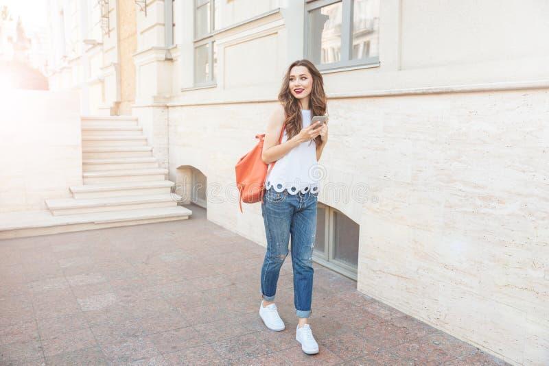 Gelukkig vrolijk jong meisje die zich met slimme telefoon bevinden royalty-vrije stock foto's
