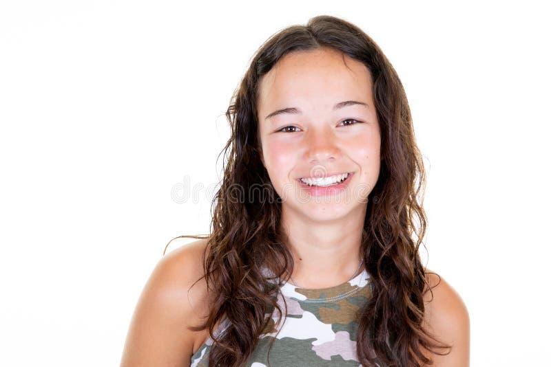 Gelukkig vrolijk jong tienermeisje met het mooie gezichtstanden lachen die camera op witte lichte achtergrond kijken royalty-vrije stock foto